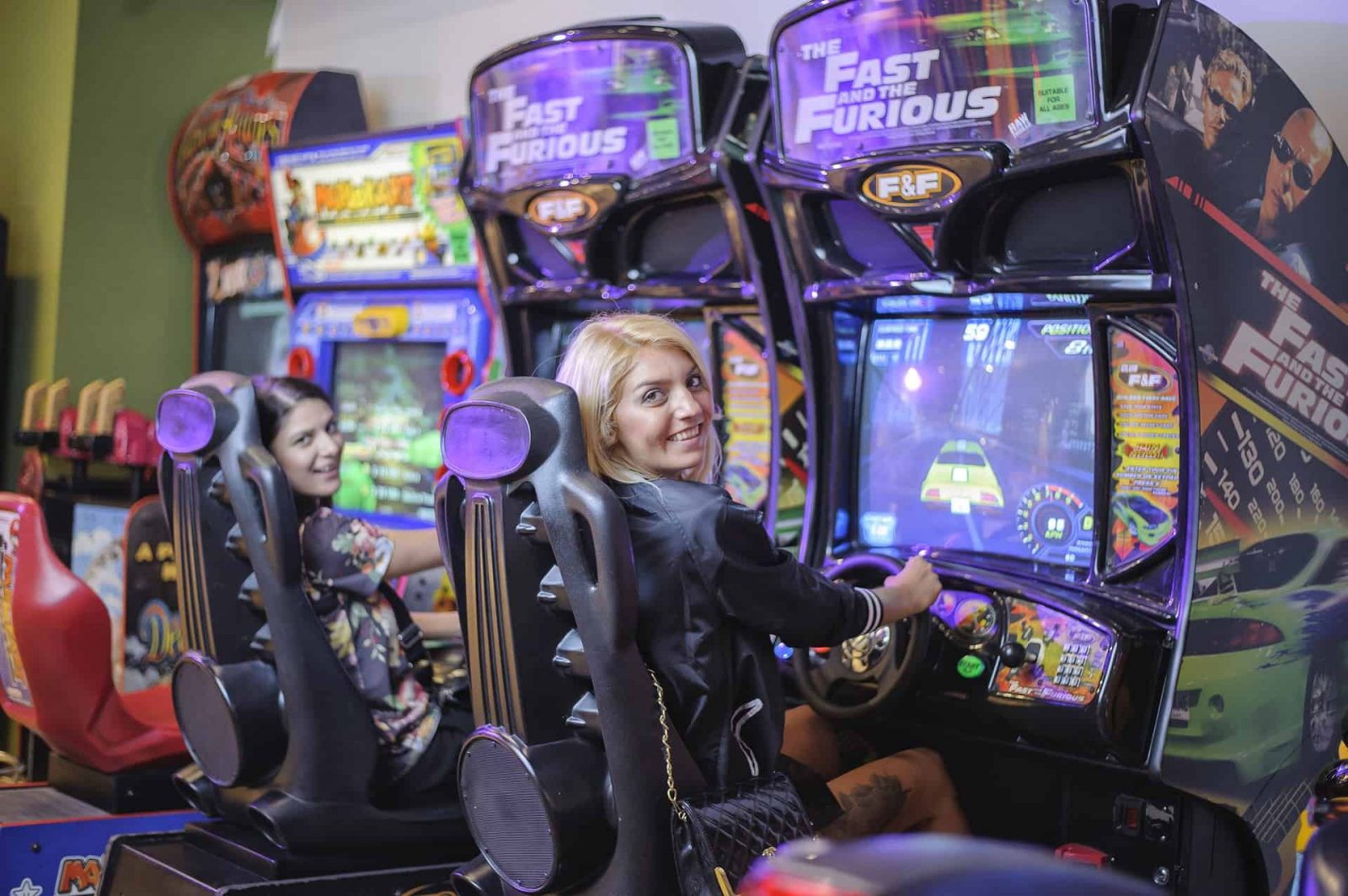 Image of 2 ladies playing Fast and The Furious Arcade Machine